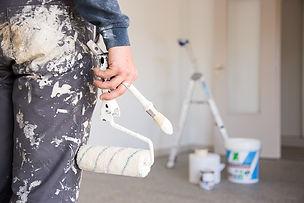 membre de l'équipe d'intervention de la société Prox tennant à la main un rouleau de peinture et un peinceau avant d'effectuer les travaux de peinture d'un salon et d'une cuisine chez un particulier en Corrèzeieure chez un particulier