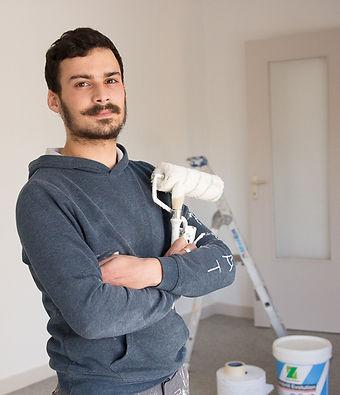 Peintre professionnel faisant parti de Prox multitravaux tennant des pinceaux et un rouleau de peinture s'apprêtant à rafraichir les murs et à repeindre les murs de cette pièce à l'intérieur d'un appartement privé en Corrèze.