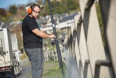 Professionnel du nettoyage de l'équipe d'intervention de Prox multitravaux en train de démousser une barrière dans l'espace public grace à l'envoi d'eau à très haute pression à l'aide d'un karcher.
