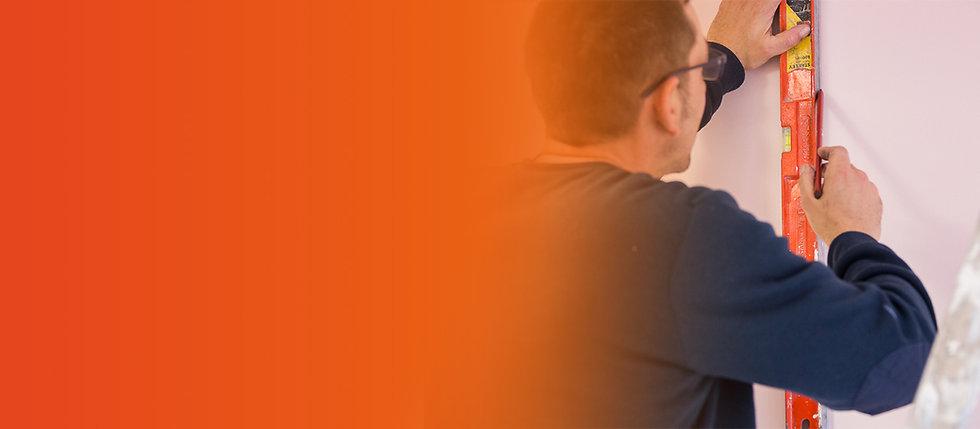"""Membre de l'équipe d'intervention """"second oeuvre"""" de l'entreprise Prox Multi-travaux en Corrèze muni d'un niveau à bulle pour tracer les repères pour la pose d'un papier peint dans une pièce de la maison d'un particulier sur le secteur d'Uzerche."""