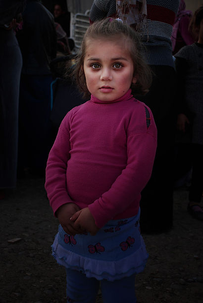 Syrian refugee waiting to collect food with other children.