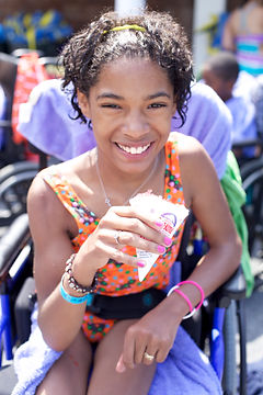 Camper in wheelchair smiles while holding a snowcone at special needs camp