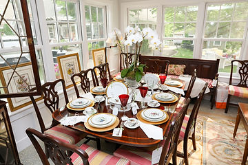 Wood dining table and chairs set with plates, glasses, and napkins