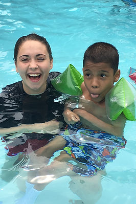 Boy wearing arm floaties with smiling councelor in pool at special needs camp