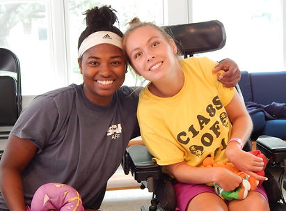 Girl in wheelchair with counselor at a special needs camp