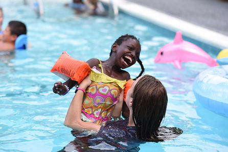 Young girl laughing as she is lifted up by a councelor while in the pool.