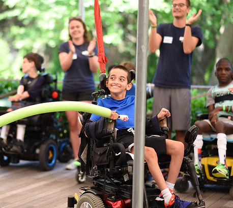 Boy in wheelchair playing a game at special needs camp