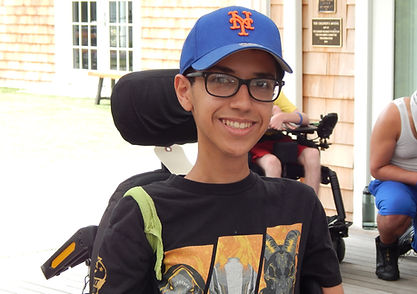 Boy in Mets cap smiling with wheelchairs in the background.