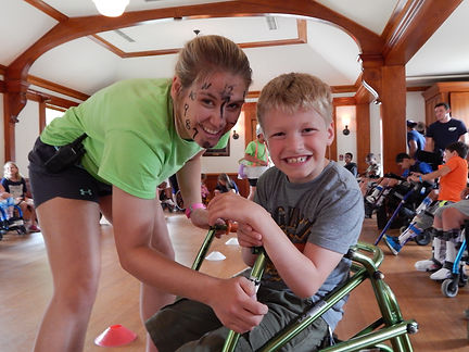 Councelor wearing facepaint smiling with a camper sitting in a walker at special needs camp
