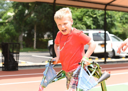 Camper using a walker playing game at camp.