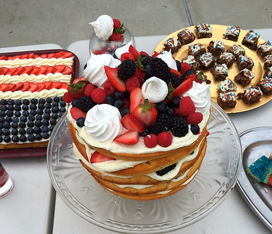 Multi layer cake covered in berries and merengues with other deserts in the background