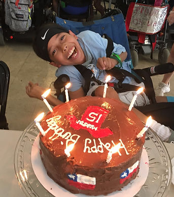 Camper in a wheelchair smiles behind a chocolate birthday cake with candles at special needs camp