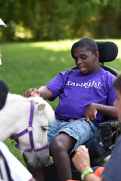 Camper in a wheel chair pets a white pony's head at special needs camp