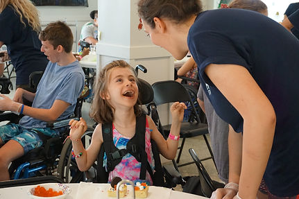 Young camper smiling excitedly at a counselor smiling back at special needs camp