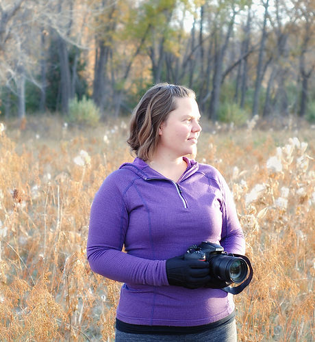 Alicia Glassmeyer, Colorado Photographer, holding a camera in a fall foiliage background.