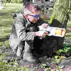 Boy crouches behind tree with nerf gun