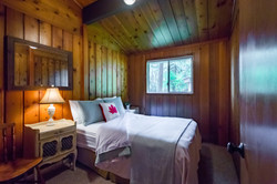 Evergreen-Double bed surrounded by warm wood.