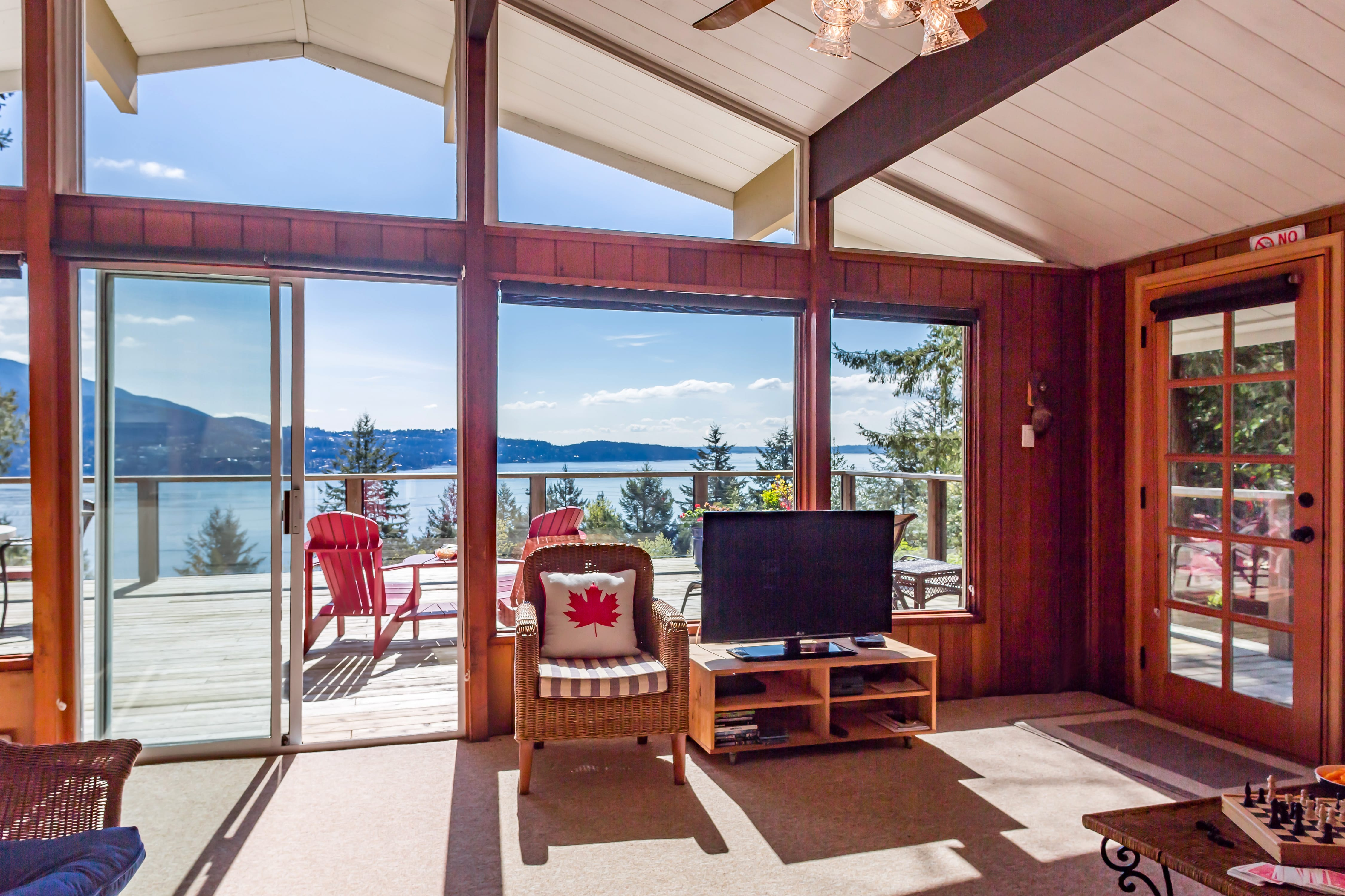 Evergreen-Living room with sunny panoramic views of ocean and decks