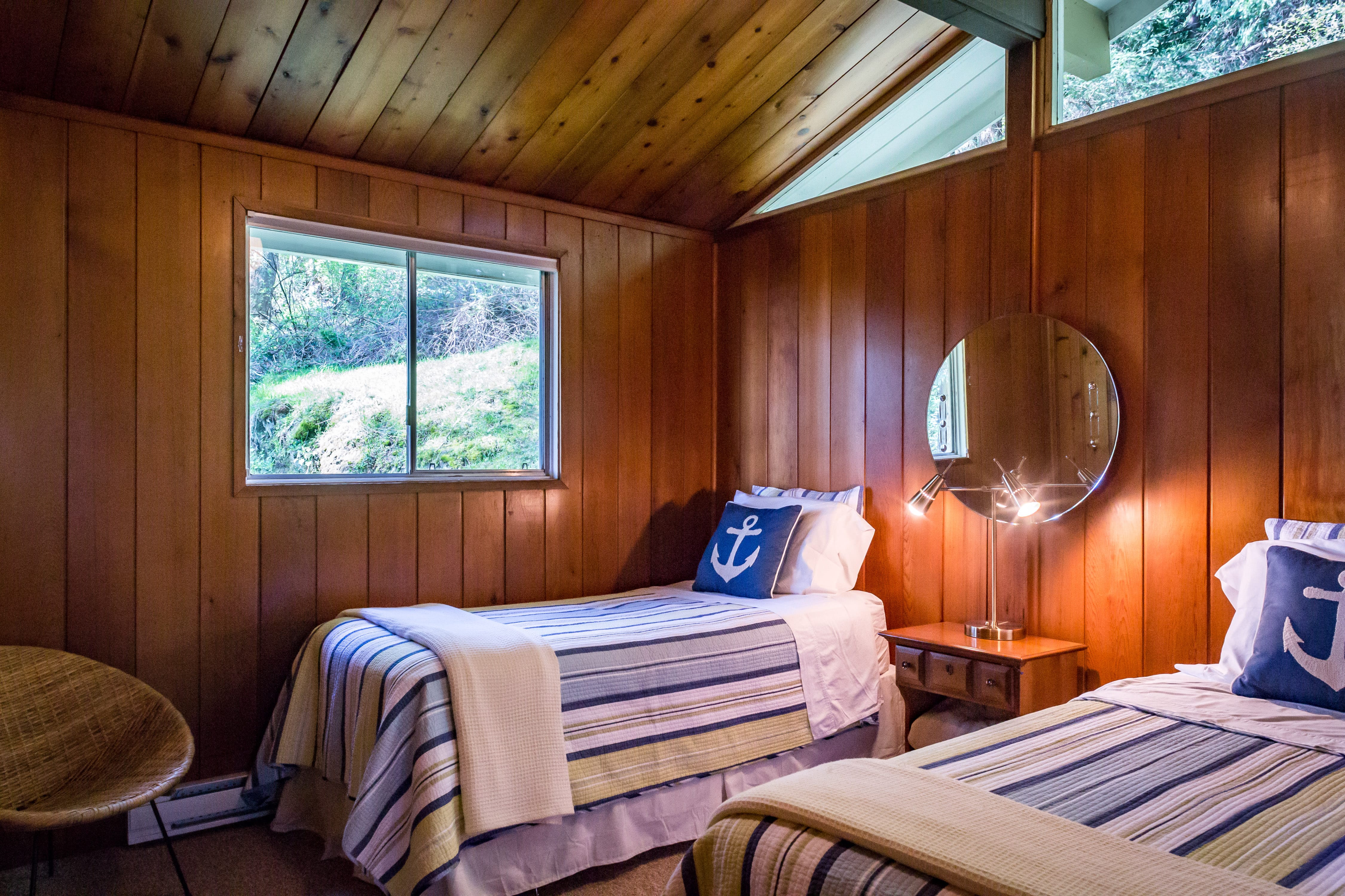 Evergreen-Twin bedroom with warm wood walls nestled among the trees