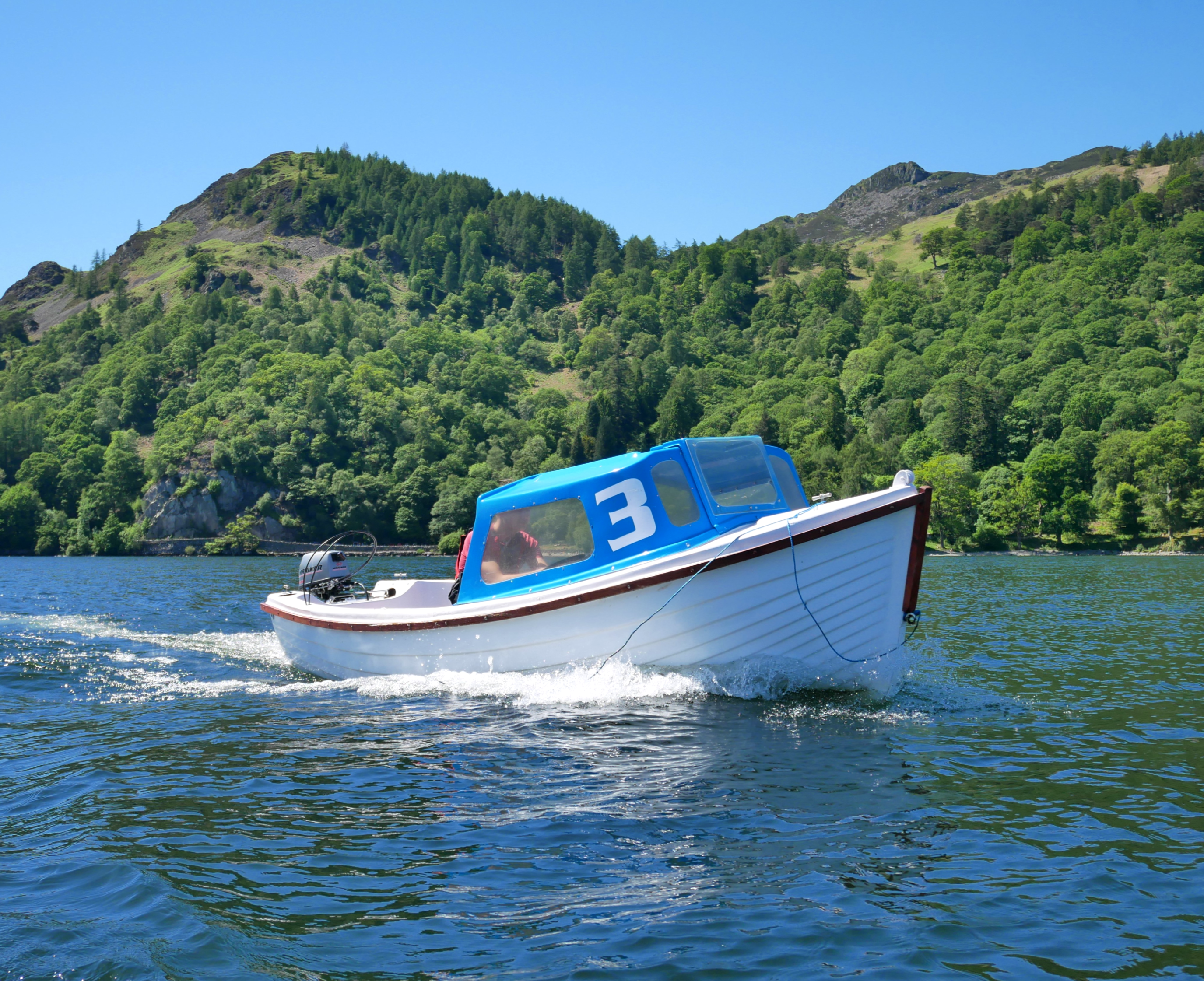 Motor boat backdropped by Glenridding Dodd & Heron Pike