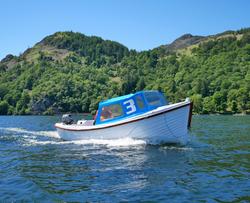 Motor boat backdropped by Glenridding Dodd & Heron Pike