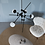 Designer asymmetrical modern chandelier in matt black color with four milk glass lamp shades over a round stone coffee table