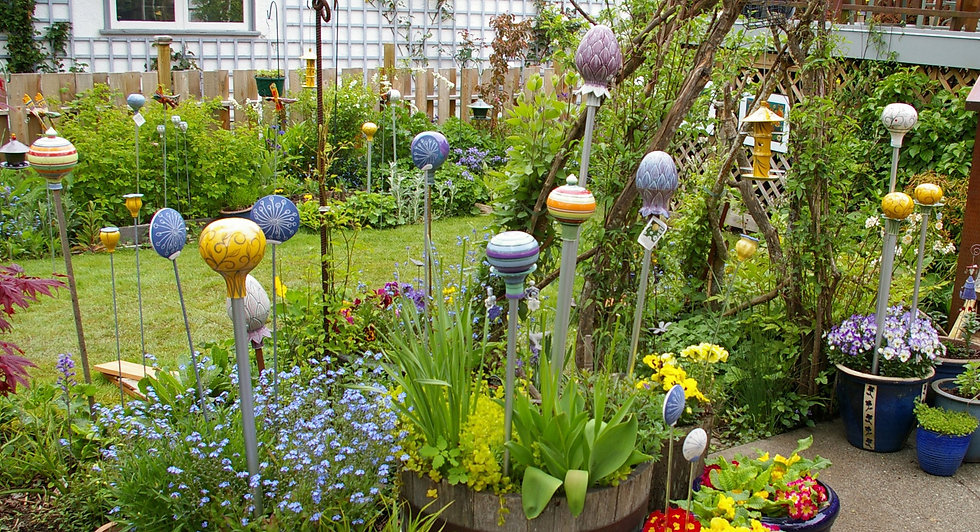 Backyard flower garden with lots of pottery balls and other shapes hanging and on poles.