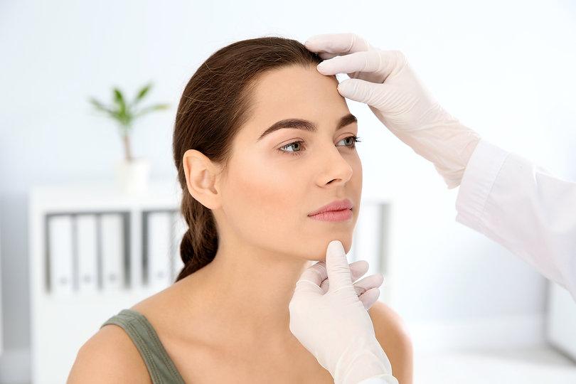 Dermatologist examining patient's face i