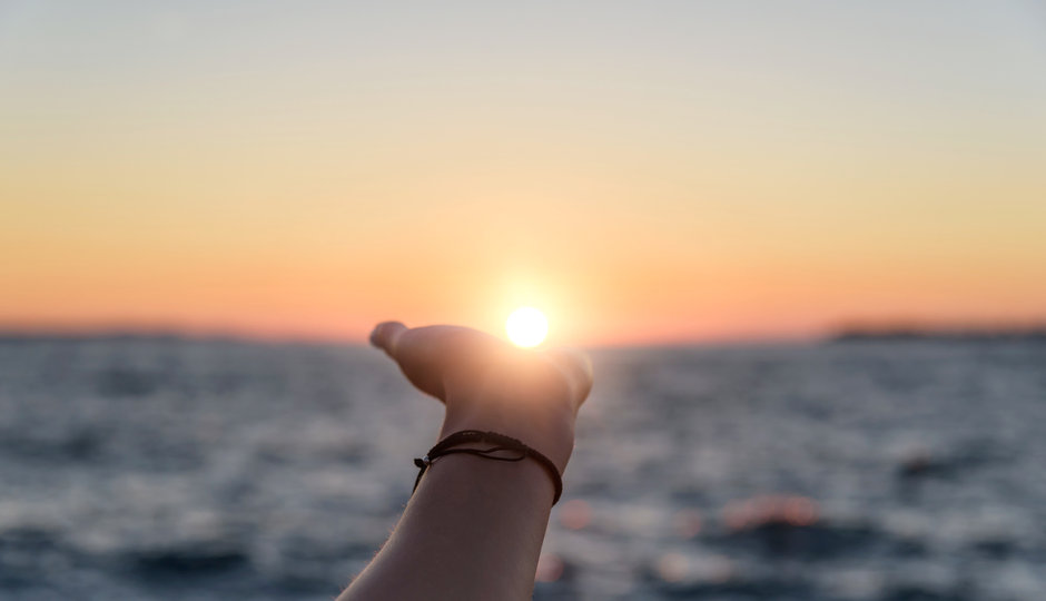 Female hand reaches for the sun at sunse