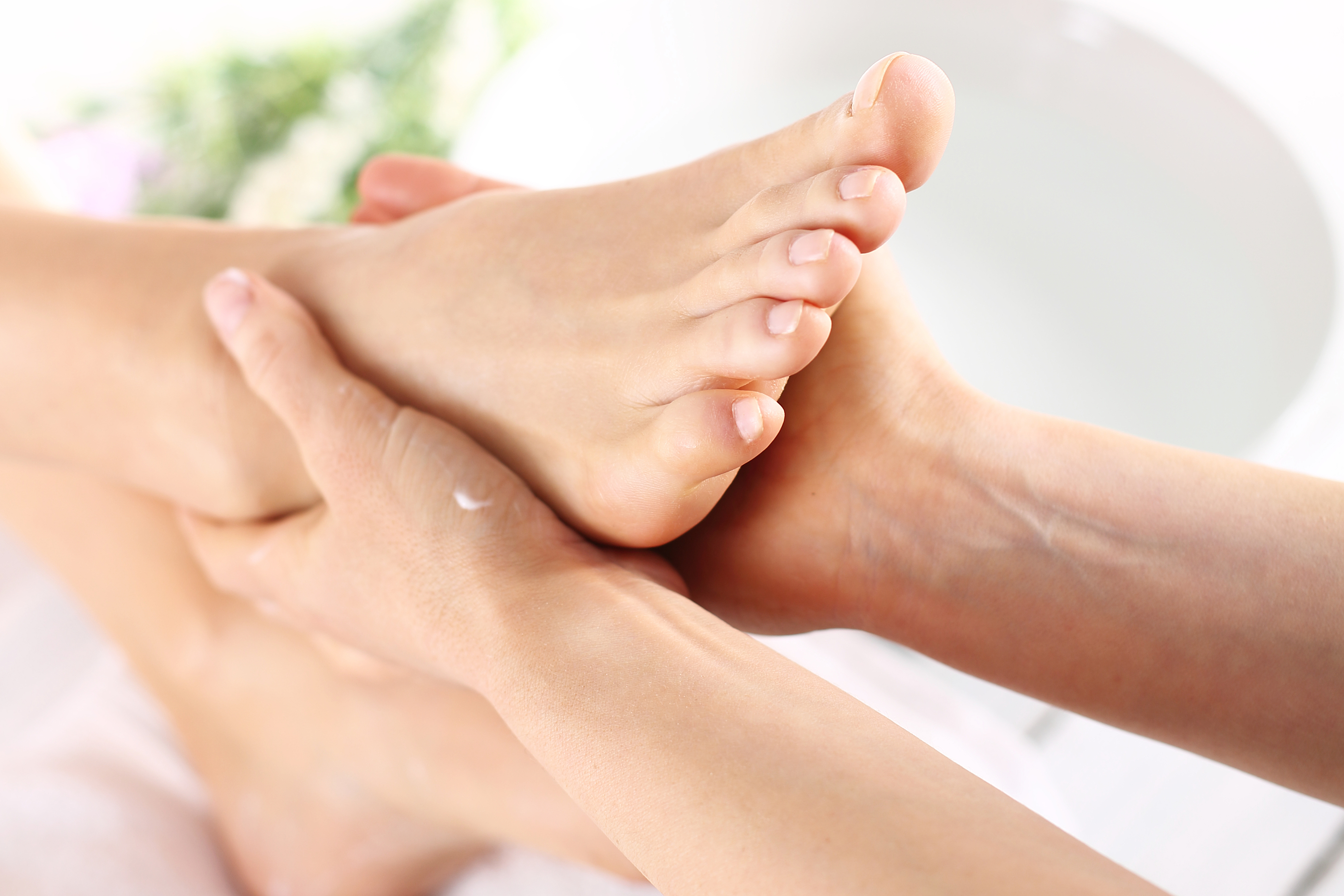 Masseuse massaging woman's foot.