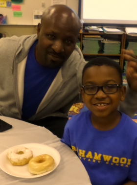 Ms. Paris' 1st graders share donuts with their dads.