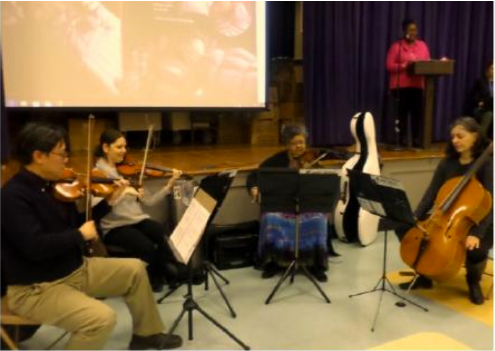 """Students at Grahamwood Elementary were treated to a performance by the Memphis  Symphony Orchestra. They played music while our very own 1 st  grade Oponal teacher Rachel  Helton read the accompanying story, I Need My Monster by Amanda Noll. """"The performance is  a part of the symphony's schools outreach program called Tunes and Tales,"""" informed  Grahamwood Or( teacher Melissa Elsholz. """"It was a wonderful experience and a great  discussion followed the program!"""" Grahamwood is proud of its long-standing tradion of  seeking out community partners who can create unique learning opportunies to expand our  students' horizons. We applaud Grahamwood's Or( Music teachers for making this possible!"""