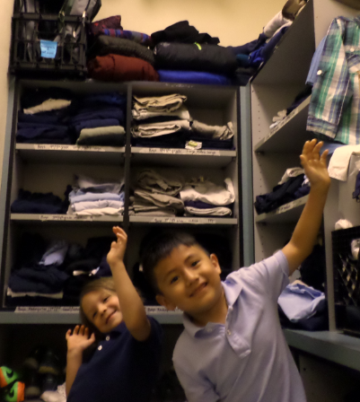 Kindergarteners Avery and Salvador show off the clean clothes in Grahamwood's clothes closet!