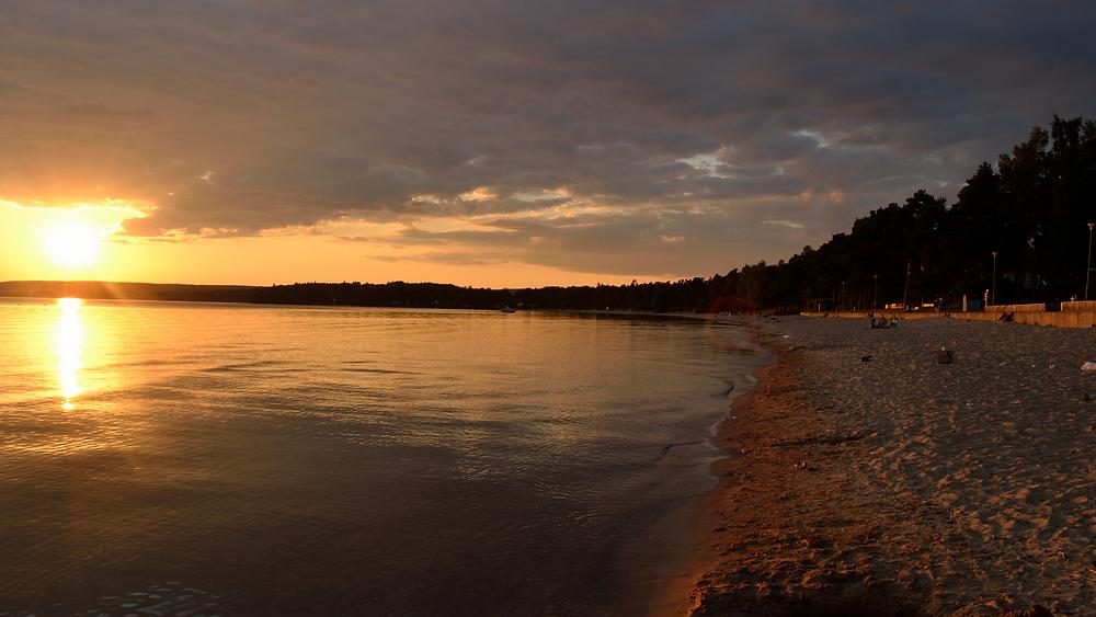 Varamon, Motala. En sandstrand med hav i solnedgången.