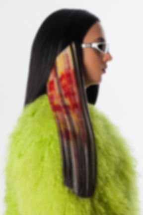Photo of woman with long brown hair with screen printed red pattern on one bleached section. Wearing white dior sunglasses and a fluffy green coat.