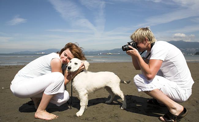 Muchacho toma fotografía cerca de mujer y mascota