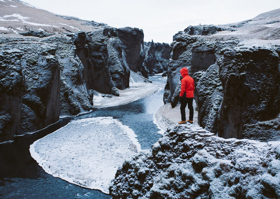 Traveler with red coat facing a cliff in the Arctic by Wix photographer Remy Brand