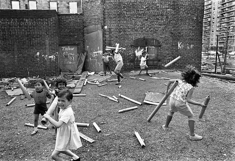 monochromatic film picture of kids playing with sticks in the street