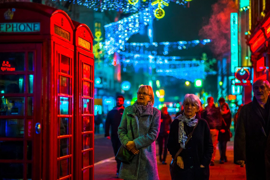 two women walk through london at night illuminated by many bright colored lights