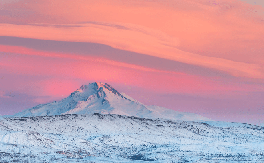 pink and orange sunset over a snowy mountain