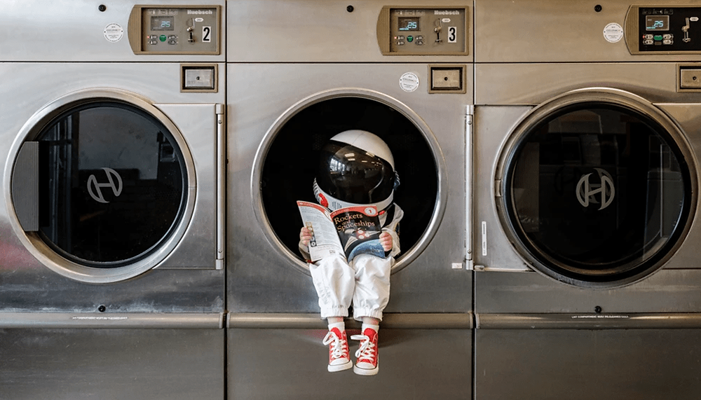 little astronaut in a laundromat