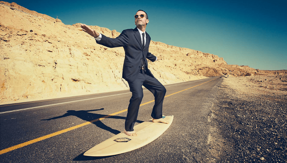 Man in a suit riding a surf board on a highwy