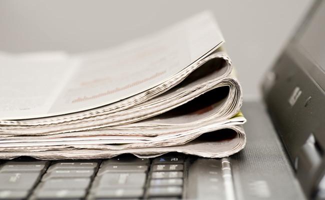 パソコンの上に新聞がのった写真