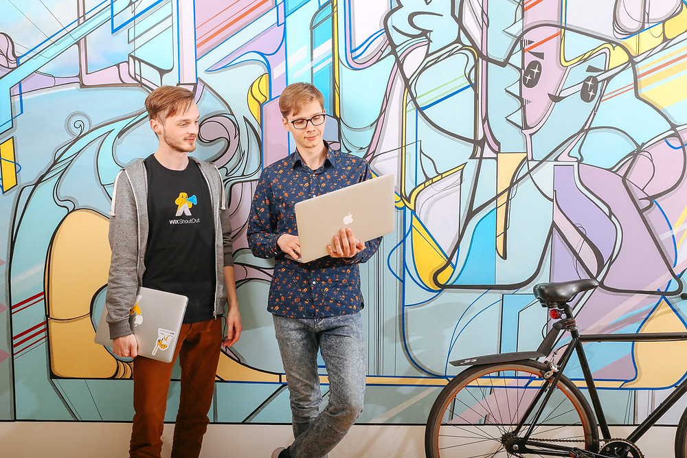 two office workers with laptops in front of a colorful wall