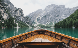 a boat on a lake surrounded by mountains
