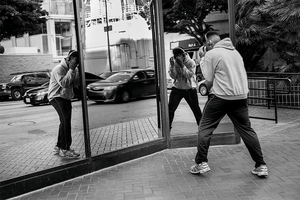 black and white image of a young man practicing moves in front of a glass wall