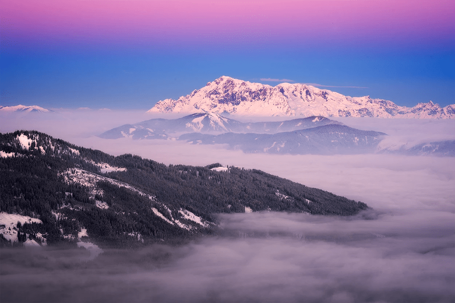 clouds over snowed mountains at sunset