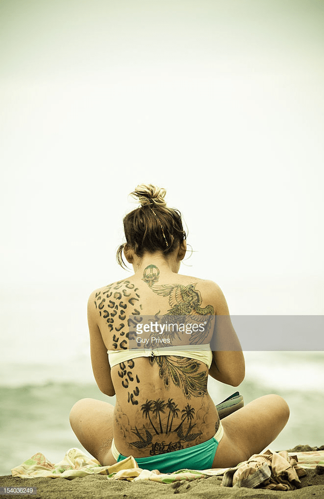 tattooed girl sitting on the beach