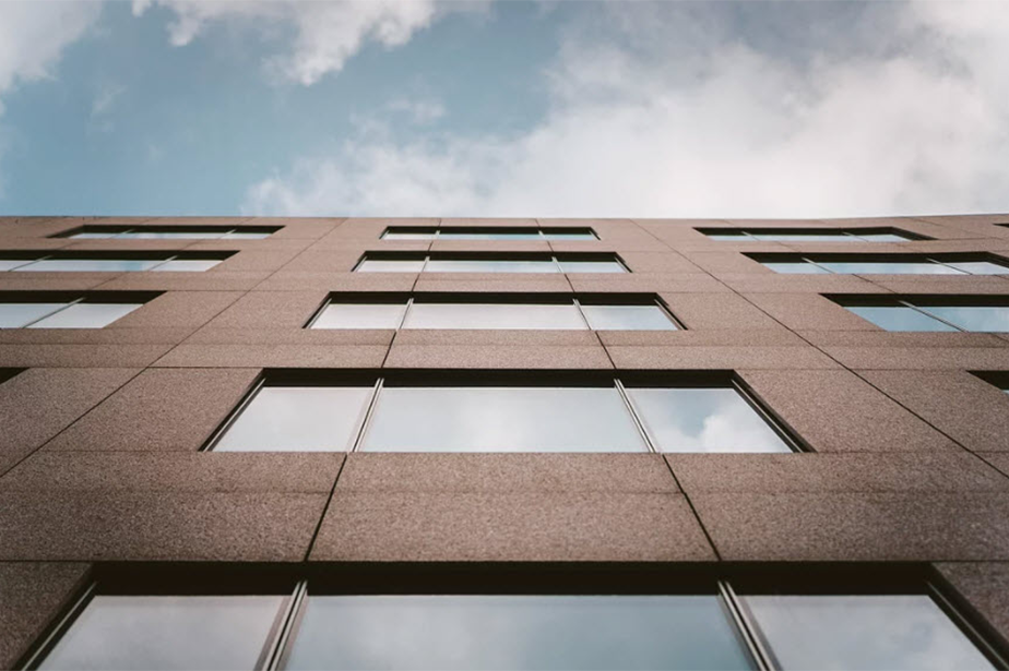 building seem from below with cloud reflecting on windows