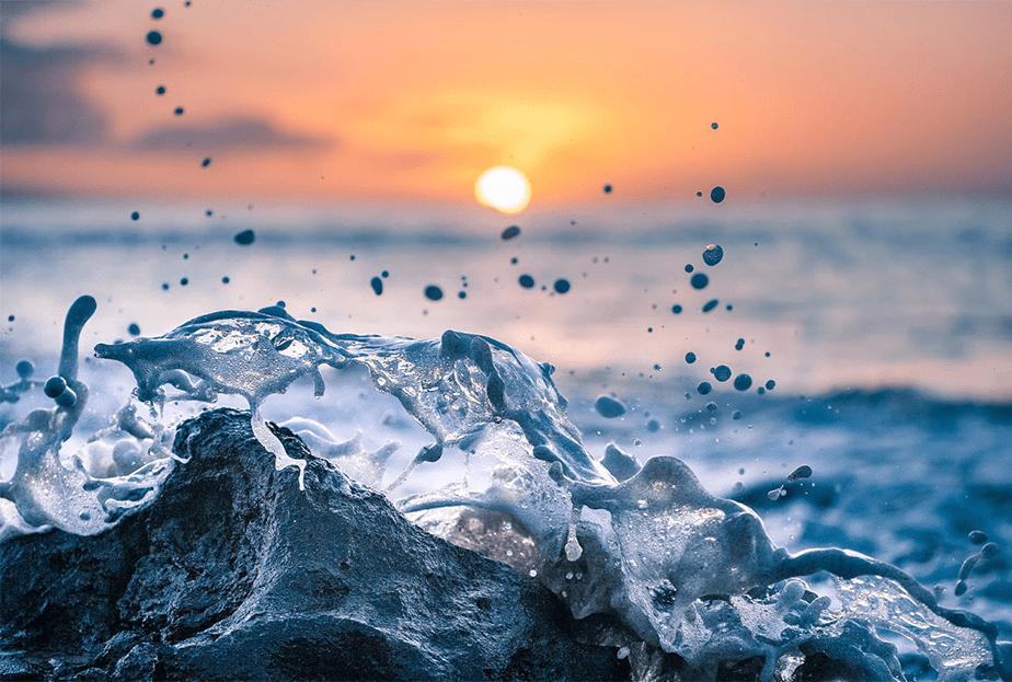 sea wave splashing on a rock as the sunset falls on the horizon